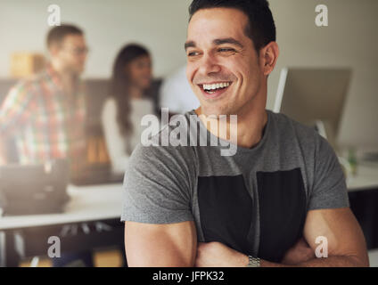 Smiling young confident man with arms crossed standing and looking away in the office. - Stock Photo