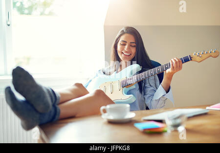 Beautiful girl singing while playing her electric guitar with feet on top of table - Stock Photo