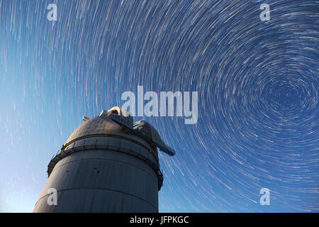 Astronomical observatory under the night sky stars. Blue sky with hundreds of stars of the Milky way. Timelapse - Stock Photo