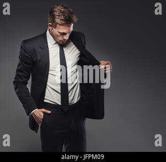Suave young businessman checking out the jacket of a stylish black suit standing alone in a studio against a grey - Stock Photo