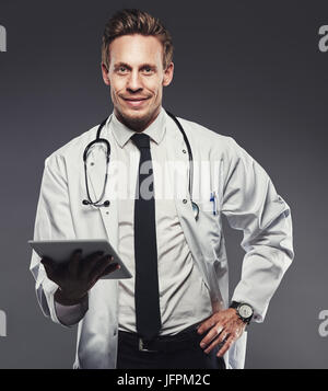 Smiling young doctor wearing a labcoat and holding a digital tablet standing alone in a studio against a grey background - Stock Photo