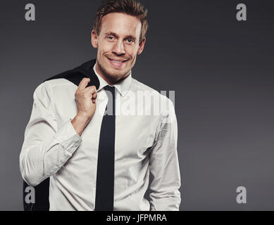 Handsome young businessman smiling and standing alone in a studio against a grey background carrying his jacket - Stock Photo