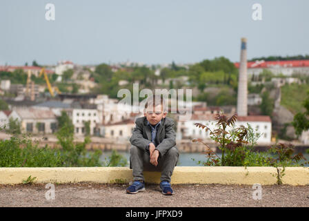 Sad little boy sitting on the curb with sea port background - Stock Photo