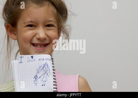 Little girl writing 'I Love my mom' - Stock Photo