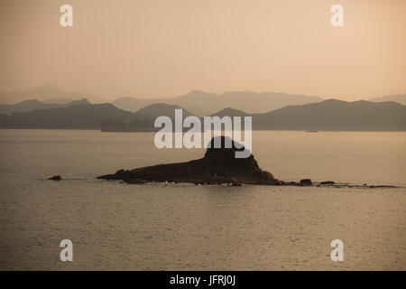 Small island in South China sea; Shenzhen, Guangdong, China; big container ship in background arriving into Yantian - Stock Photo