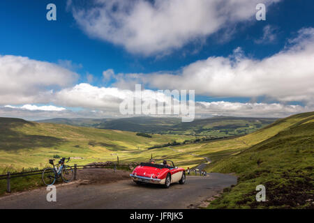 Views from top of Fleet Moss with road bike & red Austin Healey 3000 car - famous cycling hill climb & countryside - Stock Photo