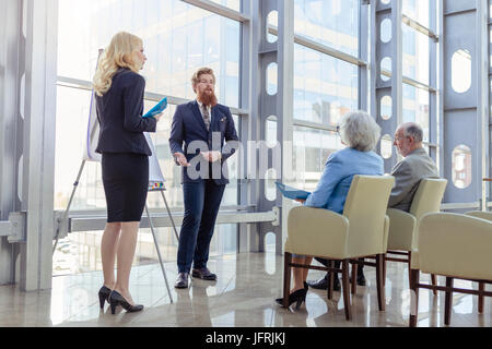 Business people making presentation to senior couple at business center, investment, investment concept - Stock Photo