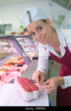 closeup of tasty red meat with female butcher smiling - Stock Photo