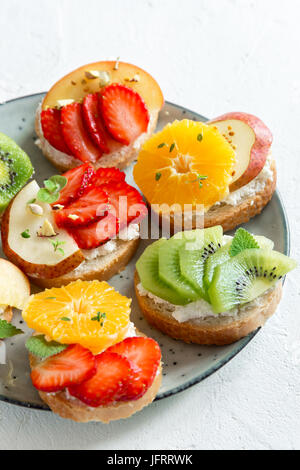 Fruit dessert sandwiches with ricotta cheese. Delicious healthy breakfast toasts with cream cheese, fresh organic - Stock Photo