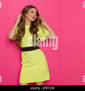 Beautiful smiling young woman in lime green dress posing with hands in hair and looking away. Three quarter length studio shot on pink background.