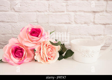 Bouquet of roses on a white desk, A large cup of coffee in front angel, Romantic floral frame background, Floral - Stock Photo