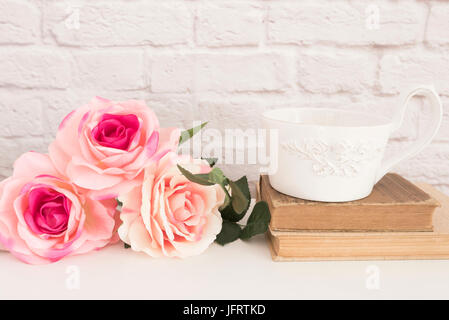 Bouquet of roses on a white desk, A large cup of coffee over old books, Romantic floral frame background, Floral - Stock Photo