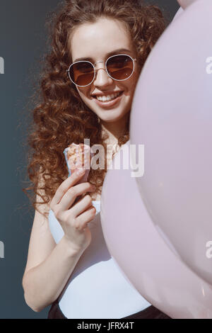 beautiful red hair girl in sunglasses eating ice cream and holding air balloons, hipster girl smiling - Stock Photo