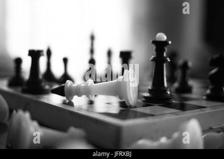 The chess pieces are placed on the chessboard. Defeated white king. The player admitted defeat - Stock Photo