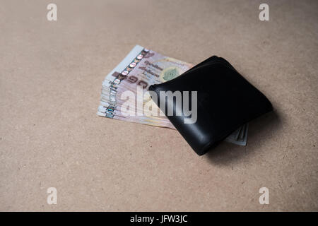 Thai money full in the black wallet on brown background - Stock Photo