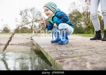 Little boy crouching on a landing pier on lake holding branch into water with his mother in background - Stock Photo