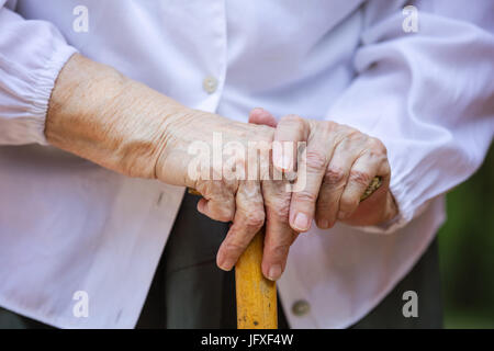 Cropped view of senior woman's hands holding walking stick outdoors - Stock Photo