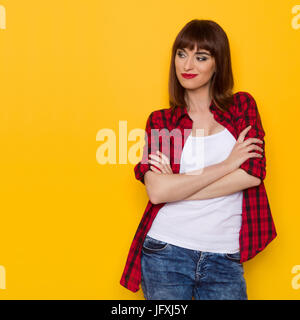 Grimacing young woman in red lumberjack shirt and jeans posing with arms crossed and looking away. Three quarter - Stock Photo