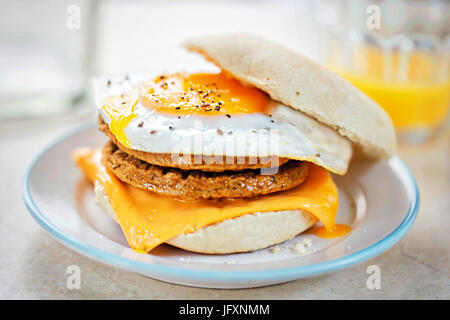 Meat free sausage flavour patties with cheese and egg on breakfast muffin - Stock Photo