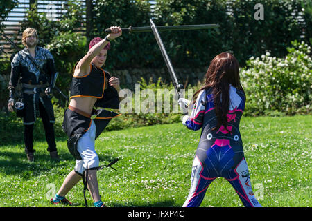 Two cosplay fans duelling with swords.  Comic book fans, film fans and cosplay fans of all ages gather at The Heartlands - Stock Photo