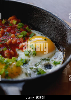 Close-up of scrambled eggs with red beans in a frying pan. English breakfast in the cafe. - Stock Photo