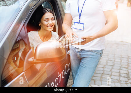 Car rental agency employee showing contract to the client - Stock Photo