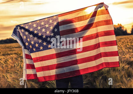 Silhoette of African American girl teenager female young woman in field of wheat or barley crops holding USA stars - Stock Photo