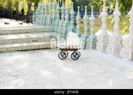 Doll's pram. Vintage doll stroller placed on the stairs to a beautiful lake. Retro cart dolls made of rattan and - Stock Photo