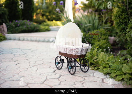 Doll's pram. Vintage doll stroller placed on the stone walkway, alley in a beautiful garden with flowers and trees - Stock Photo
