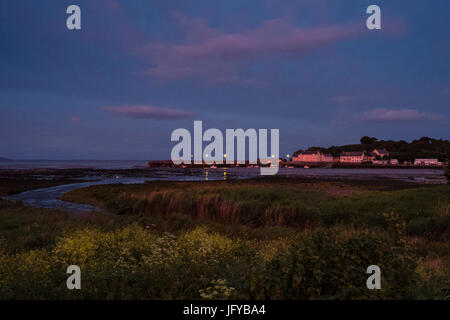 Garlieston harbour with houses and caravans turned pink by the setting sun and with yellow flowers and saltmarsh - Stock Photo