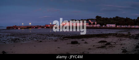 Stitched panoramic photo of Garlieston harbour with houses and caravans turned pink by the setting sun. - Stock Photo