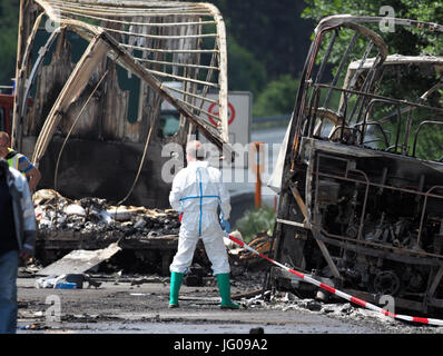 Muenchberg, Germany. 3rd July, 2017. Police experts work on the burned out shell of the travel bus at the place - Stock Photo