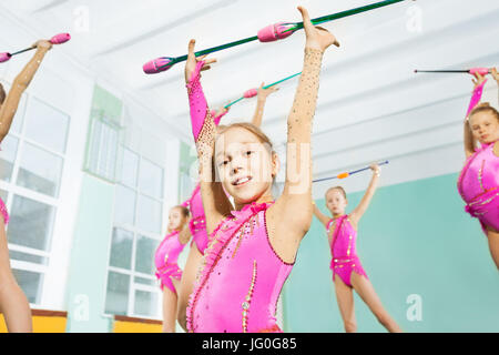 Close-up portrait of happy 11 years old girl wearing pink leotard, doing gymnastic exercises with clubs in sports - Stock Photo
