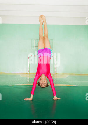 Portrait of young gymnast, 11-12 years old girl, doing handstand in school sports hall - Stock Photo