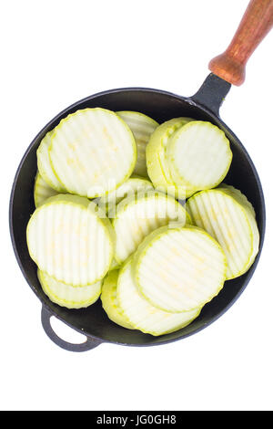 Fresh zucchini, cut into slices, in frying pan on white background. Studio Photo - Stock Photo