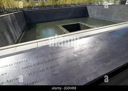 names on the north memorial pool former 1 world trade center footprint with light reflected by new one world trade - Stock Photo