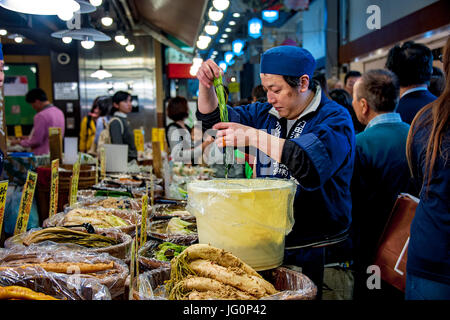 Nishiki Market, Kyoto: A crowded market. A vendor is adding more pickled vegetables to the stand. There are varieties - Stock Photo