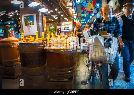 Nishiki Market, Kyoto: An old man with food in basket pushes his bicycle pass a store selling variety of pickled - Stock Photo