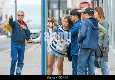 Japanese tourists looking at a street map in a city to find directions. - Stock Photo