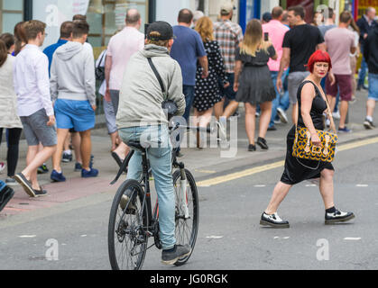 Woman crossing a road in front of a cyclist who she did not expect to be there. - Stock Photo