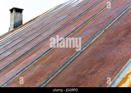 Old rusty iron metal roof with chimney - Stock Photo