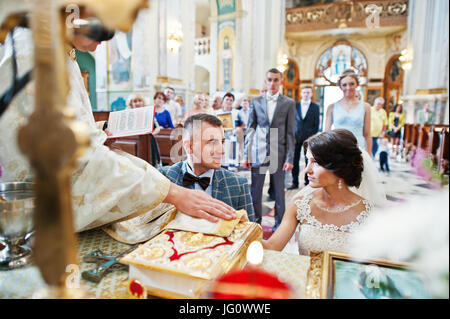 Fantastic bride and handsome groom making vows to each other in the presence of a priest in the church on their - Stock Photo