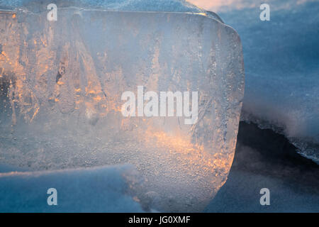A beautiful epic ice crystal on the snow in the rays of the setting sun. - Stock Photo