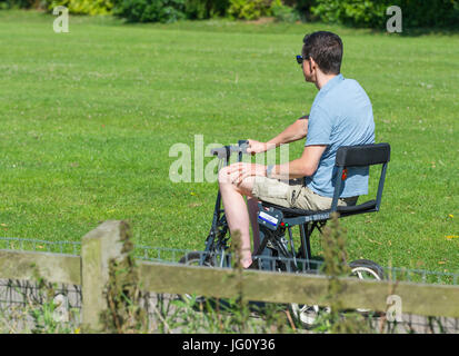 Young disabled man on an electric  mobility scooter. - Stock Photo
