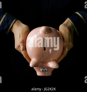 Black Mania. female hands isolated on black showing piggy bank - Stock Photo