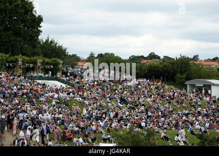 Spectators gather on Murray Mound on day one of the Wimbledon Championships at The All England Lawn Tennis and Croquet - Stock Photo