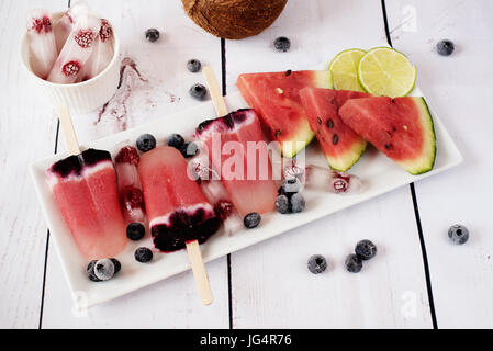 Popsicles with watermelon, coconut milk, lime, raspberries and blueberries. Popsicle on a white rectangular plateau, - Stock Photo