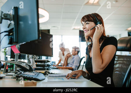 Casual businesswoman working at desk using computer and headset in the office. Focus on woman sitting in foreground - Stock Photo