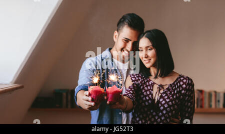 Young couple holding two cupcakes and celebrating their anniversary. Cupcakes with sparklers in hands of couple - Stock Photo