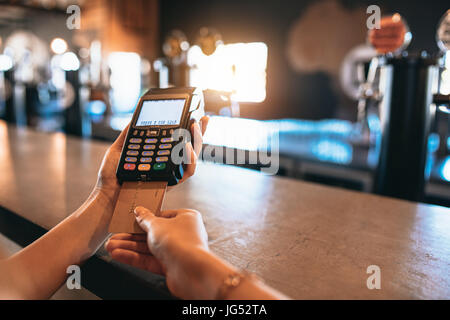 Hands of woman paying bill using a credit card at bar. Cropped shot of female at brewery factory doing cashless - Stock Photo